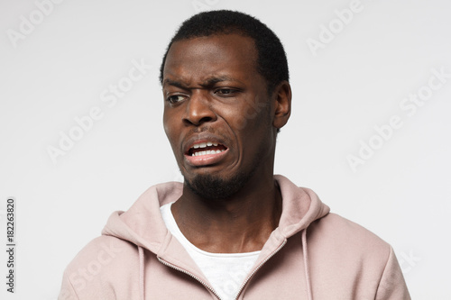 Valokuva  Disguting! Shocked young african american man looking at something unpleasant and bad, isolated on gray background