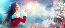 Christmas Scene. Sexy Santa. Brunette Young Woman In Party Costume Blowing Snow Over Holiday Blurred Background