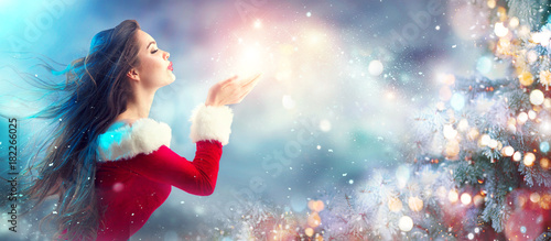 Spoed Fotobehang Kerstmis Christmas scene. Sexy Santa. Brunette young woman in party costume blowing snow over holiday blurred background