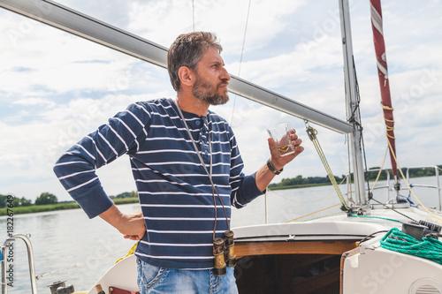 Spoed Foto op Canvas Zeilen man with beard drinks whiskey on yacht