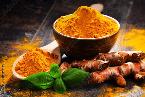 Graine, aromate Composition with bowl of turmeric powder on wooden table