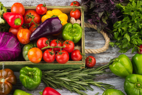Fototapeta Set of different fresh raw colored vegetables in the wooden tray, light wooden background obraz na płótnie