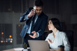 Girl and man are working late in dark office. Young beautiful girl and businesswoman in the office.