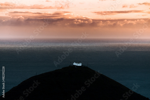 Spoed Foto op Canvas Zee zonsondergang Lonely house by the sea on Madeira Island, Portugal during sunset