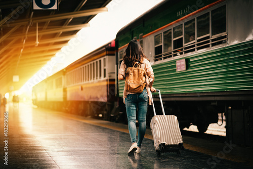 Woman traveler tourist walking with luggage at train station. Active and travel lifestyle concept