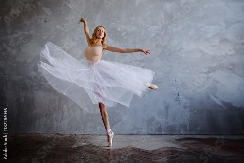 fototapeta na lodówkę Young and slim ballet dancer is posing in a stylish studio with big windows