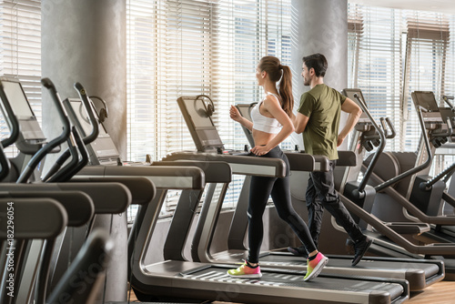 Fotografia  Frau und Mann laufen im Fitnessstudio auf dem Laufband