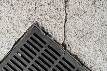 Part Of Square Storm Drain Grate Embedded In Pavement. Close Up View.