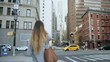 Young stylish businesswoman crossing the road in financial district of New York, America. Slow motion.