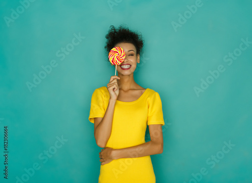 Photographie Happy mulatto girl with lollipop at studio background