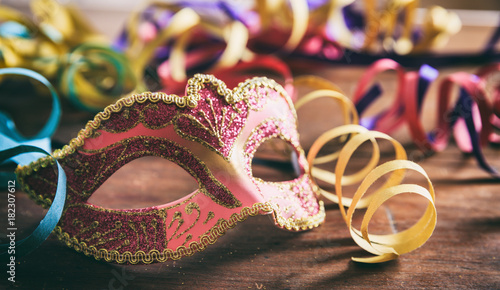Deurstickers Carnaval Carnival party. Mask and serpentines on wooden background