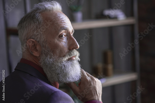 Fotografie, Obraz  Close up face of side view serene unshaven old businessman thinking while situating in modern apartment