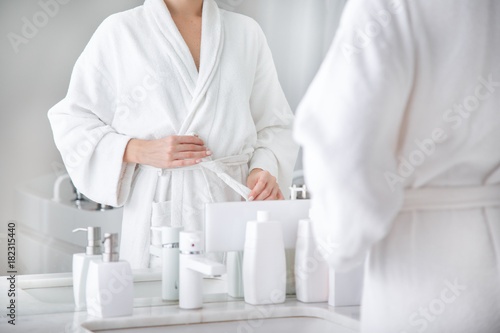 Fotografie, Obraz  Close up of body of young woman tying up belt of white bathrobe in front of the