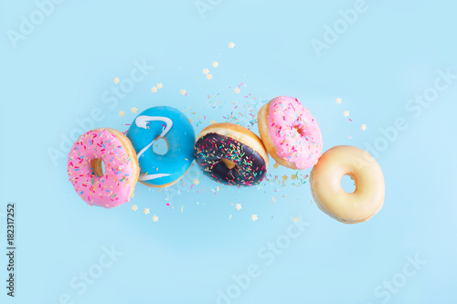 Fotografía flying doughnuts - mix of multicolored sweet donuts with sprinkles on blue backg