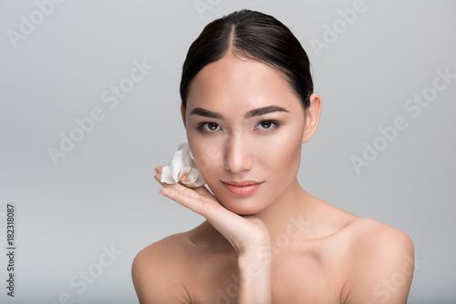 Poster Spa Keep my skin soft. Portrait of sweet enchanting young naked asian woman is looking at camera thoughtfully while leaning on palm with flower. Isolated background with copy space. Skincare concept