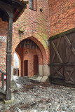 Gate in Castle of the Teutonic Order in Malbork, Poland. Red brick wall and cobblestone.