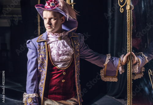 Actor dressed historical costume in interior of old theater.