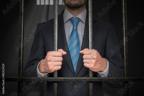 Photo Businessman or politician behind bars in prison cell.