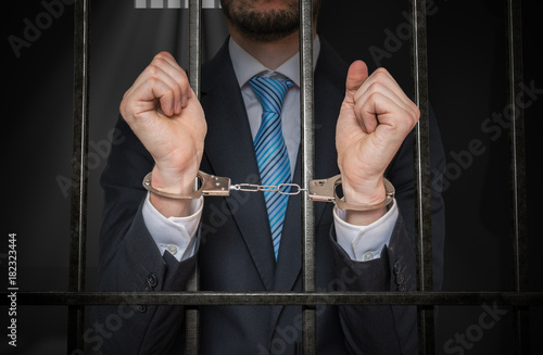 Photo Businessman or politician with handcuffs behind bars in prison cell