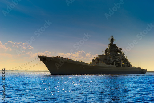Photo Stands Ship A large warship. Rocket cruiser. A military ship against the blue sky.