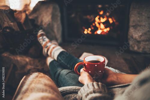 Fotografie, Obraz Woman in woollen socks by the fireplace