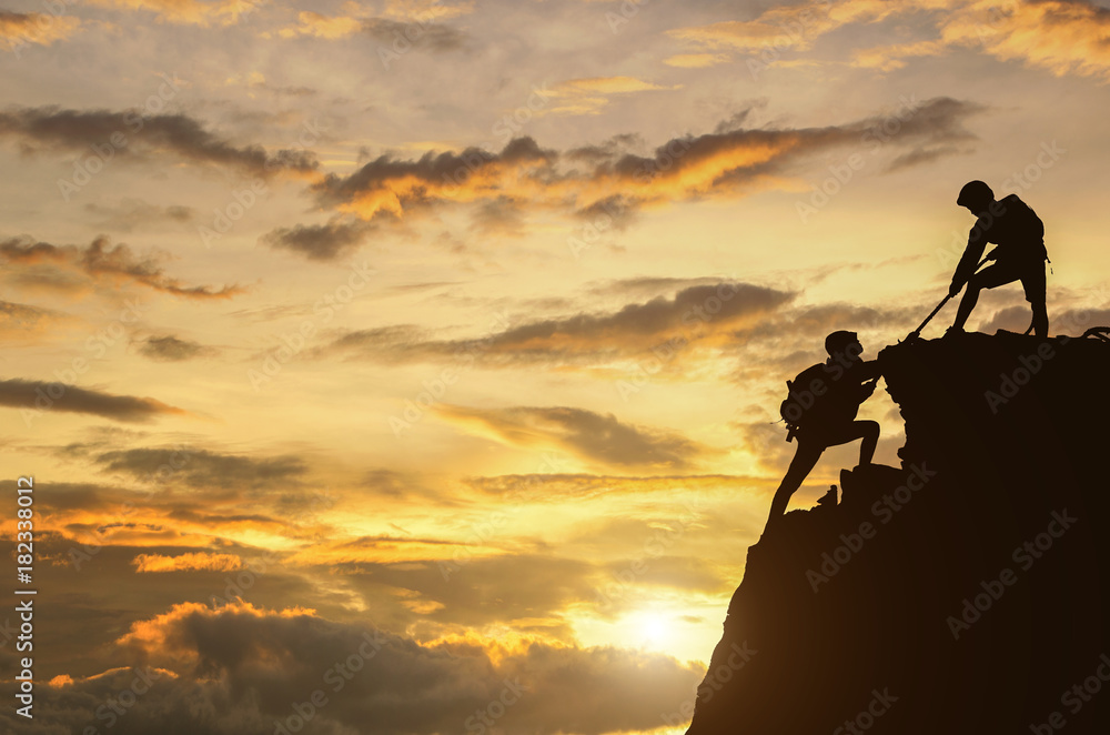 Fototapeta Male and female hikers climbing up mountain cliff and one of them giving helping hand.