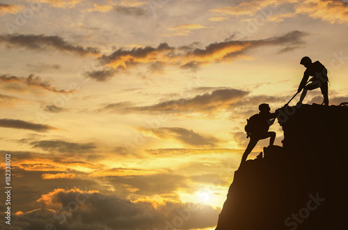 Obraz na plátně  Male and female hikers climbing up mountain cliff and one of them giving helping hand