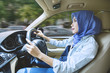 Muslim woman driving a car on the road