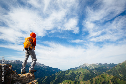 Photo Successful woman backpacker enjoy the view on top of mountain rock