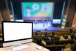 Computer set showing the white screen over the Abstract blurred photo of conference hall or seminar room with attende background, business and education concept