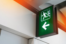 Fire Exit Sign Lightbox In The Airport Terminal Emergency Exit Way. Green Emergency Exit Sign Direction In Case Of Emergency Signage.