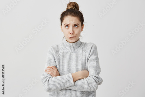 Young lady with hair in topknot standing with arms folded looking up Tablou Canvas