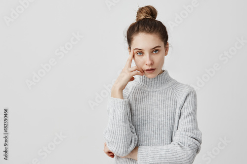 Photo Young adult girl posing with annoyed look holding finger on temple