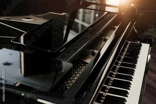 Photo Black shiny grand piano with white keyboard in dark tone