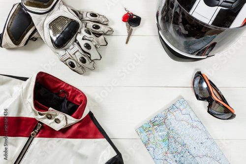 View of motorcycle rider accessories placed on white wooden table.