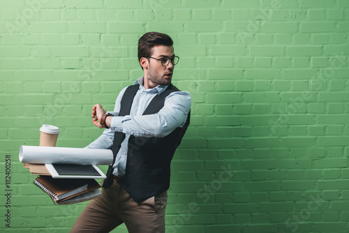 Cuadros en Lienzo young handsome busy businessman with tablet, documents and cup of coffee in fron