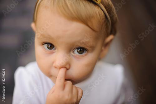 Valokuva  Cute little baby girl picking her nose