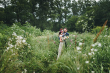The Bride And Groom Went Deep Into The High Grass In The Summer Park And Gently Embrace.