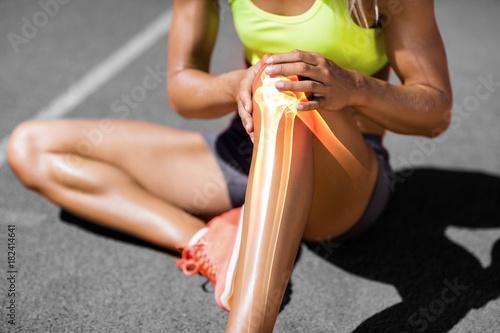 Low section of sportswoman suffering from knee pain Fototapet