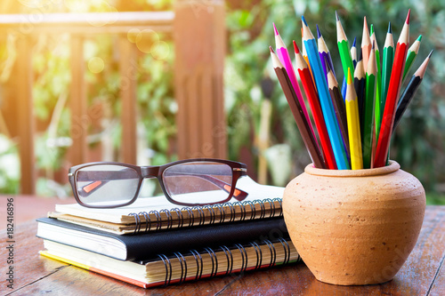 Valokuva  Assortment color pencil in pot and eyeglasses on stack book on rustic wooden table with copy space