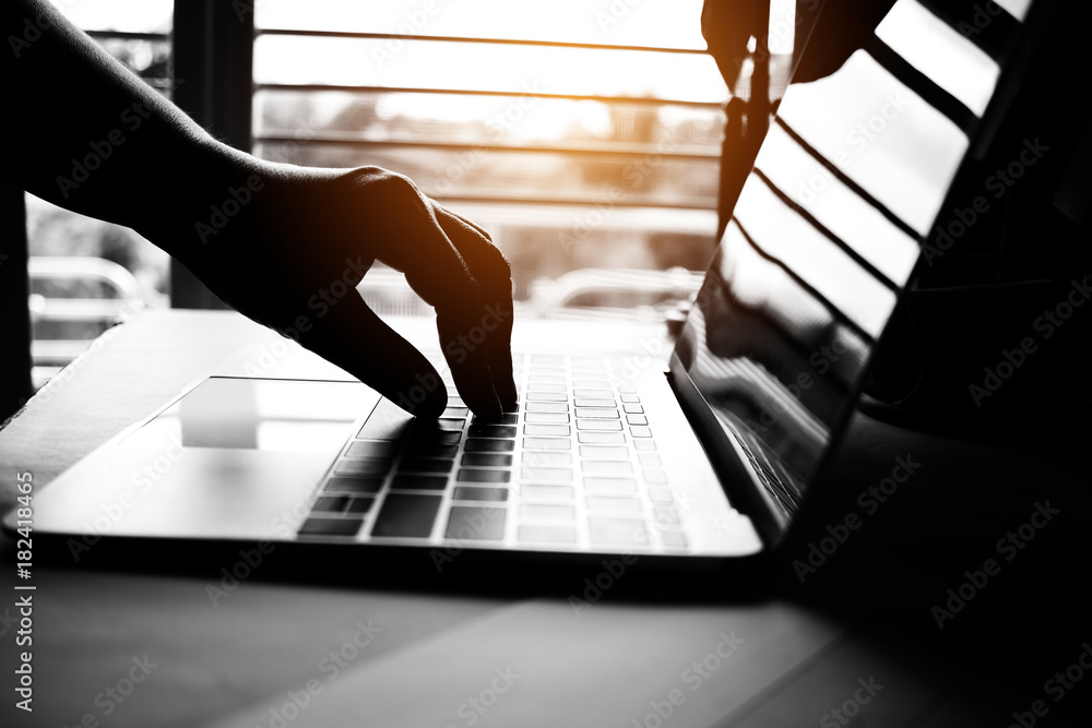 hands of anonymous hackers typing code on keyboard of laptop for remotely reach and receiving personal information online networking, Internet Crime Payment Security Concept, Silhouette black white