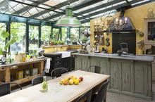 Cuisine Installée Dans Un Jardin D'hiver D'une Ancienne Maison Et Son Mobilier Chiné Trouvé En Brocante Pour Un Style Vintage