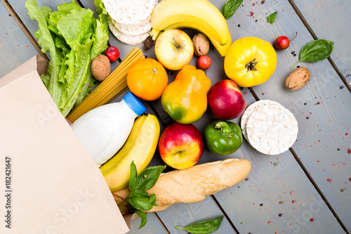 Fototapeta Grocery shopping concept. Different food in paper bag on wooden background.  Flat lay. obraz na płótnie