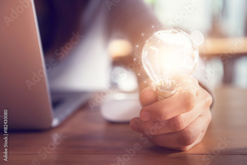 Photo  Closeup hand holding light bulb while using on laptop, New ideas and creativity concept
