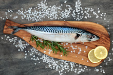 Mackerel Fish Health Food On An Olive Wood Board With Course Salt, Rosemary Herb And Lemon Fruit On Marble Background. High In Omega 3 And Good For Maintaining A Healthy Heart.