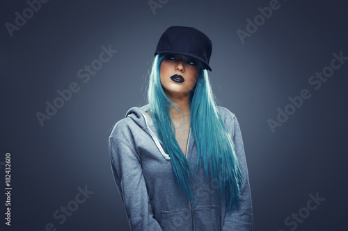 Fotografie, Obraz  Young woman with cyan color hair in hoodie and cap