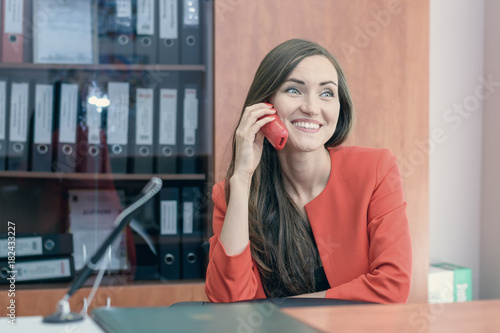 Fotografie, Obraz  A young girl in a red suit sits back at work, talking on the phone with friends