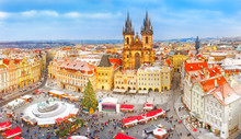 Prague, Czech Republic, Bohemia. Christmas Market In Stare Mesto Old Square. View On Snow Classic Red Roofs, Christmas Fair, Christmas Tree In Center Of Square, Tyn Church. Iconic Landmark In Europe.