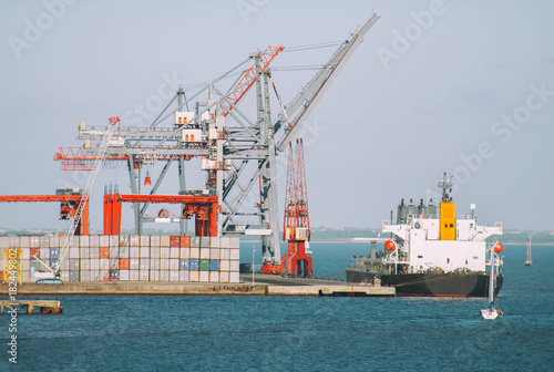 Industrial sea port with containers and cranes and ship.