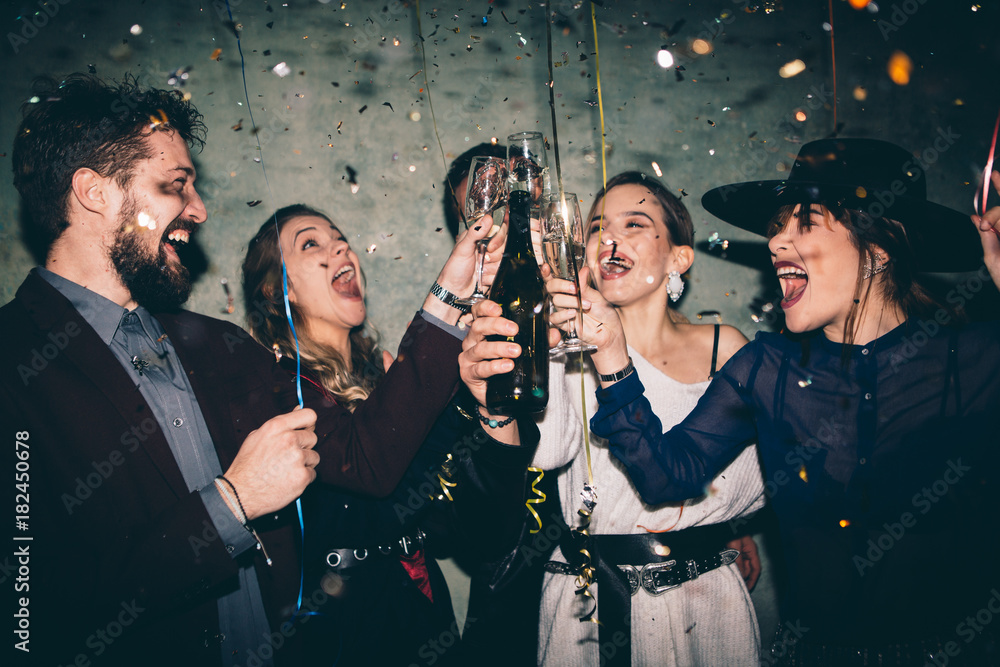 Fototapeta Group of happy friends drinking champagne and celebrating New Year. New year party. Birthday party